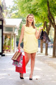 Beautiful urban girl standing on the street after shopping — Stock Photo