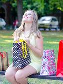 Mujer joven divirtiéndose en el parque después de ir de compras — Foto de Stock