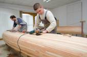 Young carpenters assembling new canoe — Stock Photo