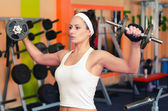 Young female bodyduilder lifting weights in the gym. — Stock Photo