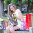 Beautiful young woman having fun in the park after shopping — Stock Photo #57386685