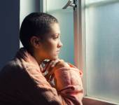 Young cancer patient standing in front of hospital window — Stock Photo