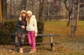Two beautiful girls having fun outdoor on sunny autumn day — Stock Photo