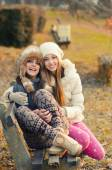 Two beautiful girls sitting on the bench outdoor on sunny autumn — Stock Photo