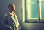 Bald woman suffering from cancer looking throught the hospital w — Stock Photo