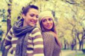 Two beautiful girlfriends having fun in the park on colorful aut — Stok fotoğraf