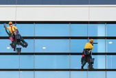Two workers washing windows of the modern building — Stock Photo