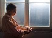 Young female cancer patient standing in front of hospital window — Stock Photo