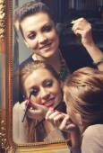 Beautiful girls having fun while putting make up in front of the — Stock Photo