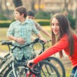 Teenage girl having fun on bicycles with her friends in the park — Stock Photo #68799071