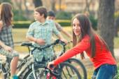 Teenage girl having fun on bicycles with her friends in the park — Stock Photo