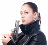 Beautiful girl in black leather jacket and beretta gun in her ha — Stock Photo