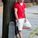 Handsome teenage boy with skateboard standing beside tree on str — Stock Photo #71275977