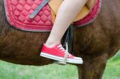 Detail of the teenage girl sitting on the horse on spring day — Stock Photo