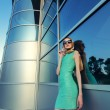 Beautiful fashionable urban girl standing in front of modern office building — Stock Photo #73061821
