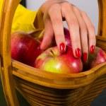 Elegant female hand picking apple from wooden basket — Stock Photo #74578553