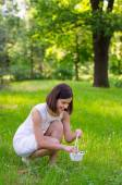 Beautiful girl in white dress and small basket walking in forest picking flowers — Stock Photo