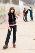 Pretty smiling girl on roller skates posing outdoor with friends in autumn — Stock Photo