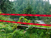 """Two Strips of Red """"Danger"""" Tape in a Wilderness Scene — Stock Photo"""