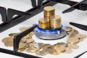 Golden coins on gas cooker  — Stock Photo