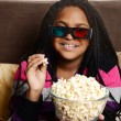 Child eating popcorn watching 3d movie — Stock Photo #57652493