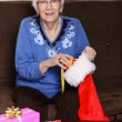 Senior stuffing christmas stocking — Stock Photo #58660937