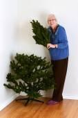 Senior woman with fake christmas tree — Stock Photo