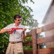 Man is cleaning wooden fence — Stock Photo #60347205