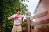 Man is cleaning wooden fence — Stok fotoğraf