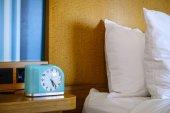 Bed and a bedside table with alarm clock — Stock Photo