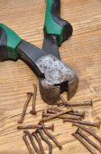 Rusty pliers and nails on a wooden table — Foto Stock