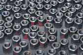 Shiny metal nuts on a metal surface — Stock Photo