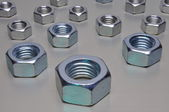 Group of steel nuts with green light reflection — Stok fotoğraf