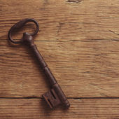 Old key on a wooden background — Stock Photo