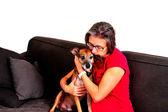 Woman cuddling with dog on a grey sofa — Stock Photo