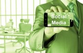 Business man hand holding smartphone with Socail Media — Stockfoto