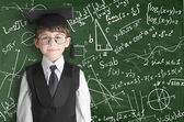 Boy near blackboard with formulas — Stock Photo