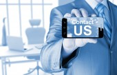 Business man hand holding smartphone with the message contact us — 图库照片