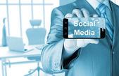 Business man hand met smartphone met socail media — Stockfoto