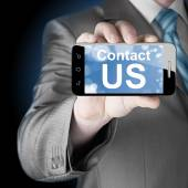 Business man hand holding smartphone with the message contact us — Photo