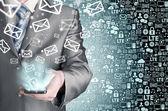 Hombre de negocios sosteniendo teléfono inteligente y enviar correos electrónicos — Foto de Stock
