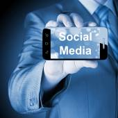 Business man hand holding smartphone with Socail Media — Stock Photo