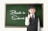 Cheerful little boy on blackboard. Looking at camera — Stock Photo