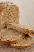 Whole grain bread isolated on wood background — Stock Photo