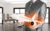 Businessman holding airplane — Stock Photo