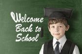 Cheerful little boy on blackboard. Looking at camera — Stock Photo