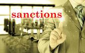 Businessman pressing sanctions button on virtual screens — Stock Photo