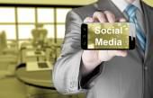 Mão de homem de negócios segurando smartphone com monitoramento de mídia — Fotografia Stock
