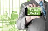 бизнес человек рукой, держащей смартфон с socail сми — Стоковое фото
