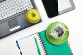 Green apple on worplace — Stock Photo